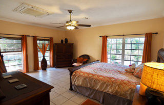 Master Bedroom with King bed, air conditioning and LCD TV with view on the palms garden