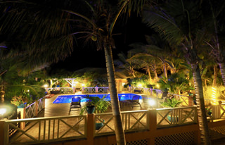 villa tropica pool deck and chromatic pool at night